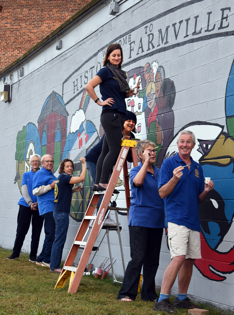 Rotarians help paint a mural for Historic Farmville